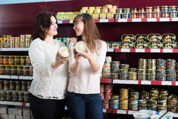 Customer choosing canned goods in store.