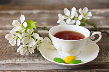 cup of tea with a sprig of apple on a wooden background