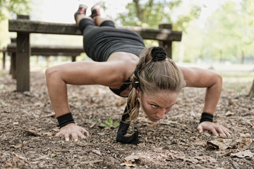 Push ups. Attractive female athlete exercising, doing push-ups in park.