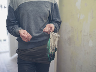 Young woman in hallway with garden gloves