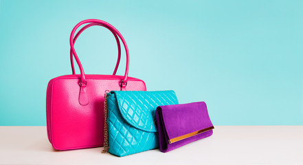 Colorful bags with light blue background. Copy space. Leather products.