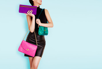 Woman holding many colorful bags. Isolated on light blue. Shopping. Fashion image.