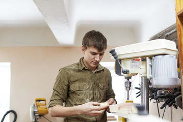 Young carpenter drilling wood element
