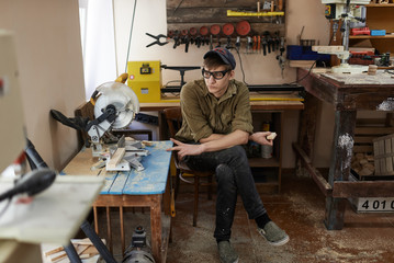 young carpenter , In goggles in the workshop wondered own small business for the production of wood products