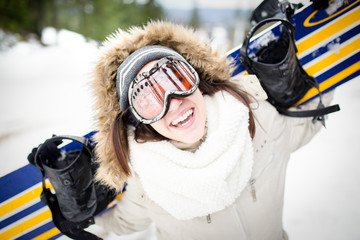Close up of young beautiful woman with ski mask holding her snowboard at ski slope Young woman in ski resort holding snowboard on her shoulders and smiling.Concept of winter holiday