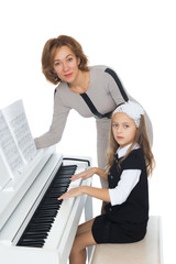 Mother and daughter learning to play piano - Isolated on white background