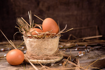 .raw eggs in a nest of hay and grass .