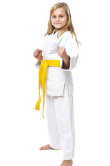 Portrait of a karate girl in kimono with yellow belt ready to fi