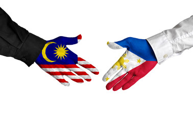Malaysia and Philippines leaders shaking hands on a deal agreement