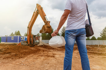man in jeans, holding a helmet in her hand and looks on an excavator
