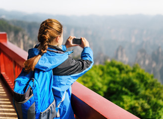 Young female tourist taking photo of scenic mountains