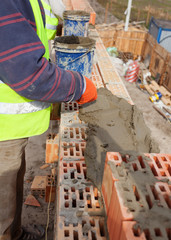 Worker building brick walls at house construction site, bricklayer and cement
