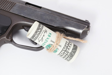 Black gun is lying on dollar bills