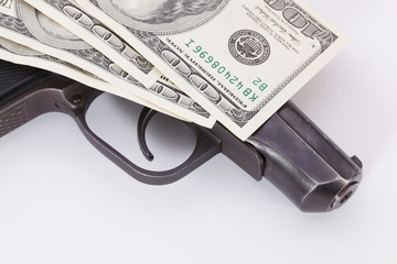 Black gun is lying on dollar bills