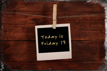 Photo paper with text Today is Friday 13 on wooden background