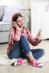 Young pretty girl listening to music on the floor in her room
