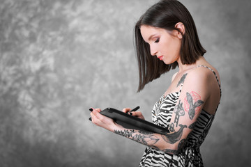 Woman with tablet on grey wall  background