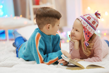 Cute children read book on the floor in the decorated Christmas room