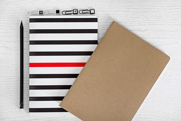 Notebooks with pencil and clips on a table