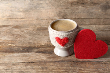 Coffee cup with milk and heart on wooden background closeup