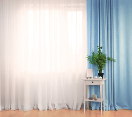 Small white table with green plant and frame on curtain background