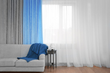 Grey sofa and small table with lamp on curtain background