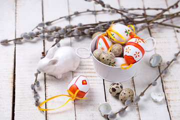 Decorative easter eggs , rabbit and  willow  branches on wooden