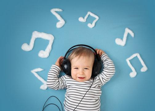 little boy on blue blanket background with headphones