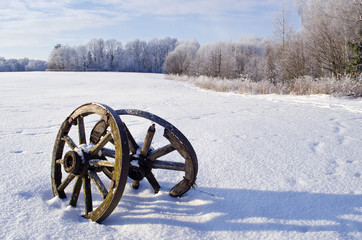 Snow covered field with two antique wooden wheels