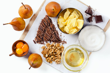 Food ingredients for making cake with chocolate and pears