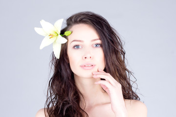 Woman with curly hair and big blue eyes touching lips. Woman with a flower in her hair.