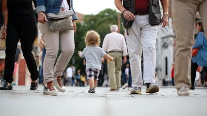 Baby boy walking in crowd