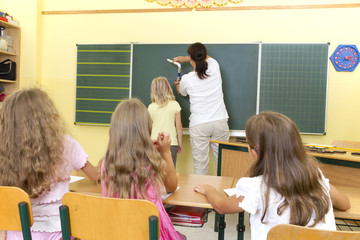 Photo shows a teacher in front of a classroom. Behind the teacher is a blackboard. Studiolight