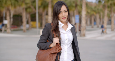 Fashionable young woman carrying a large handbag standing smiling at the camera outdoors against an urban park or square with palm trees