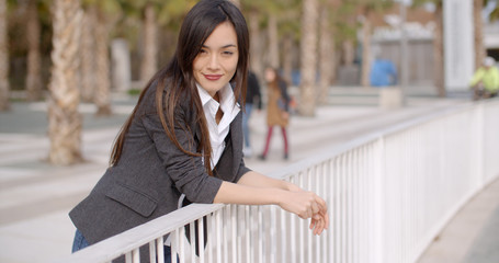 Relaxed thoughtful young woman leaning on white metal railings outdoors in an urban park looking to the side with a pensive smiling expression