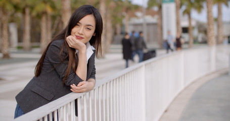 Young thoughtful woman leaning on a white metal railing in an urban environment looking to the side with a pensive expression