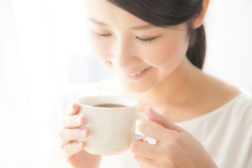 コーヒーを飲む女性 笑顔 窓際