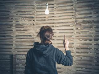 Young woman having idea under light bulb