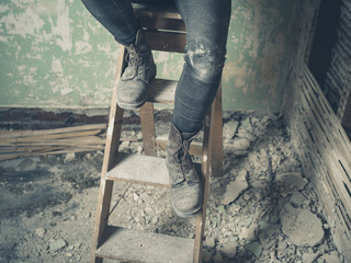 Legs of person sitting on stepladder
