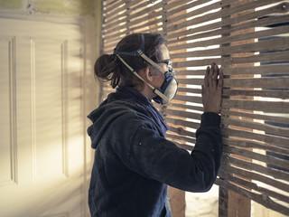 Young woman peeping though wattle and daub wall