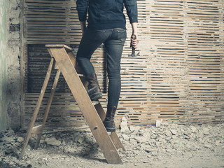 Woman standing on stepladder by wattle and daub wall