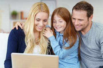 eltern schauen sich gemeinsam mit ihrer tochter etwas am laptop an