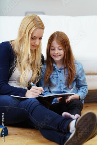 junge frau hilft einem kind bei den hausaufgaben imagens. Black Bedroom Furniture Sets. Home Design Ideas