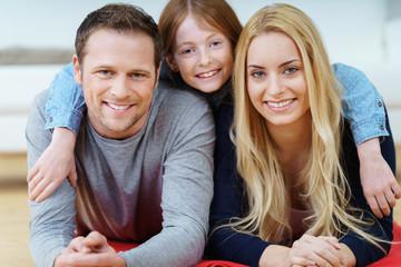 glückliche junge familie liegt auf dem fußboden im wohnzimmer