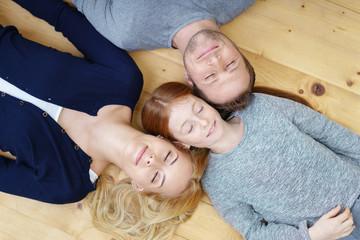 familie liegt entspannt auf dem fußboden und träumt