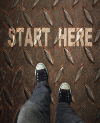 Pair of sneakers on road with print of word start for the concept of starting point