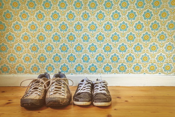 Two pair of old dirty shoes in front of retro wallpaper