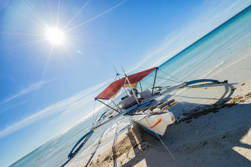 Philippines traditional fishing boat in the clear sea waters on Bantayan island on the blue sky background with shining sun. Wide angle shoot.