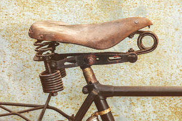 Detail of a rusted ancient bicycle with leather seat