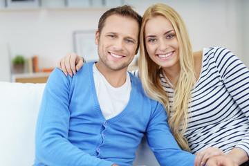 glückliches paar sitzt auf dem sofa und umarmt sich